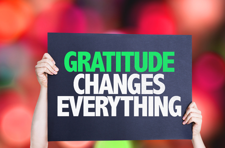 thankfulness: Hands holding Gratitude Changes Everything card with bokeh background Stock Photo