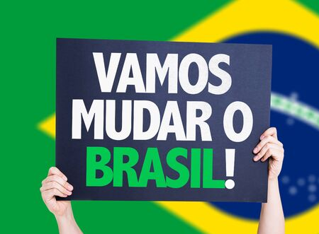 patriot: Hands holding Lets Change Brazil (in Portuguese) card with brazil flag