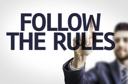 businessperson: Business man pointing to transparent board with text: Follow the Rules