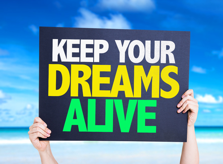 alive: Hands holding Keep Your Dreams Alive card on beach background