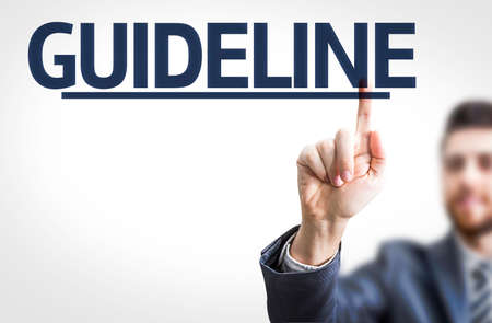Business man pointing to transparent board with text: Guideline