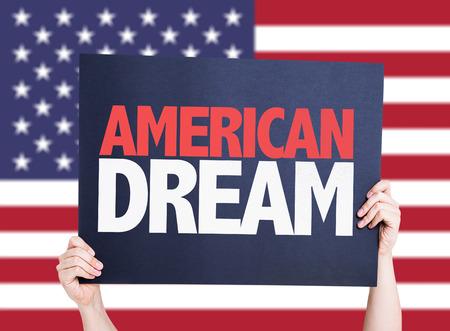 Hands holding American Dream card on America flag background Foto de archivo