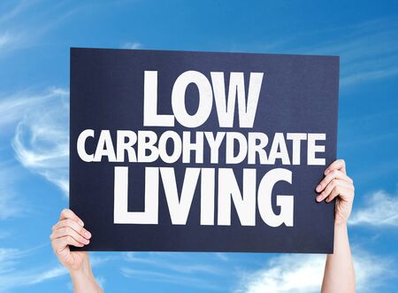 carbohydrate: Hand holding cardboard with text Low Carbohydrate Living on sky background Stock Photo