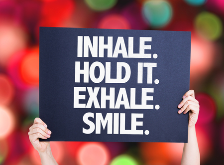 exhale: Hands holding Inhale Hold It Exhale Smile card with bokeh background