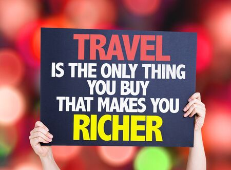 richer: Hands holding Travel is the Only Thing you Buy that Makes you Richer card with bokeh background Stock Photo