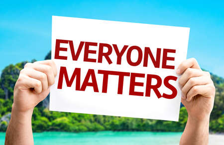 everyone: Hands holding Everyone Matters card with island background Stock Photo