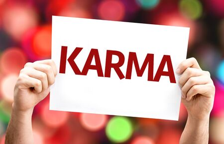 karma: Hands holding Karma card with colorful background with defocused lights