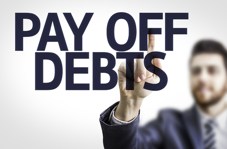 cast off: Business man pointing to transparent board with text: Pay Off Debts Stock Photo