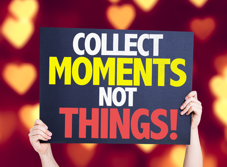 collect: Hands holding card with text Collect moments not things on heart bokeh background Stock Photo