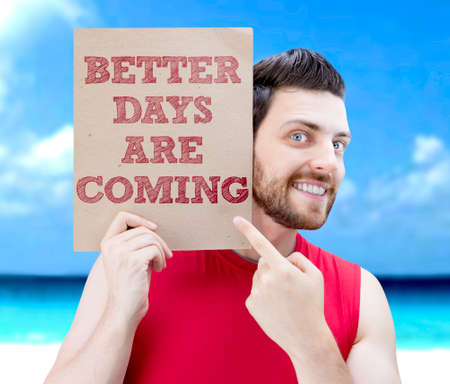 better days: Man holding card with text Better Days Are Coming on beach background