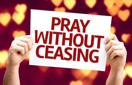 ceasing: Hands holding Pray Without Ceasing card with heart bokeh background