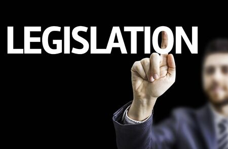 lawfulness: Business man pointing the text Legislation with black background