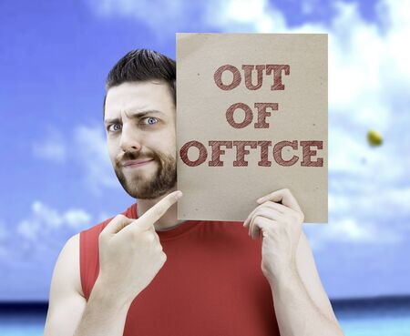 man holding card: Man holding card with text Out Of Office on beach background Stock Photo