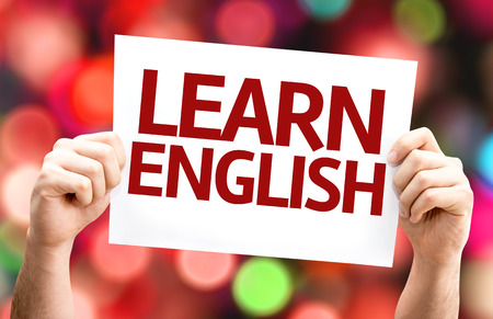idiomas: Manos que sostienen la tarjeta con el texto Aprende Inglés en el fondo del bokeh