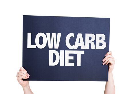 Hands holding card with text Low carb diet on white background