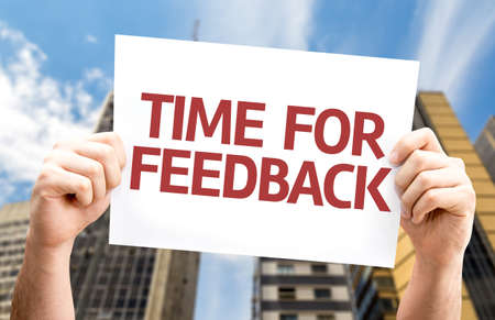 valued: Hands holding card with text Time for feedback on building background Stock Photo