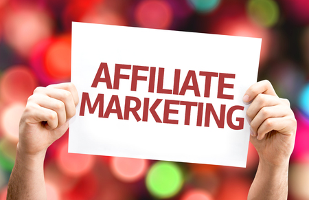 affiliates: Hands holding card with text Affiliate marketing on bokeh background