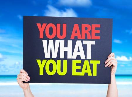 what to eat: Hands holding cardboard with text You Are What You Eat on beach background