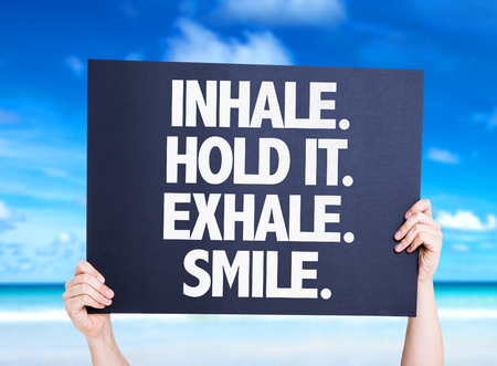exhale: Hands holding cardboard with text Inhale Hold It Exhale Smile on beach background