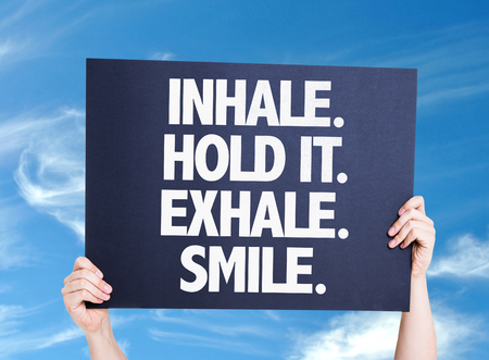 exhale: Hands holding cardboard with text Inhale Hold It Exhale Smile on sky background