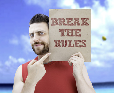 man holding card: Man holding card with text Break The Rules on beach background Stock Photo