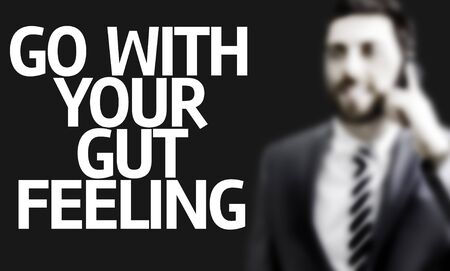 instincts: Business man with the text Go With Your Gut Feeling on black background Stock Photo