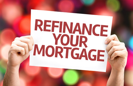 refinance: Hands holding cardboard with text Refinance Your Mortgage on bokeh background