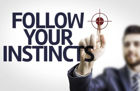 instincts: Business man pointing the text Follow Your Instincts