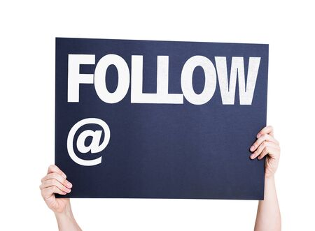 newsfeed: Hands holding cardboard with text Follow At on white background