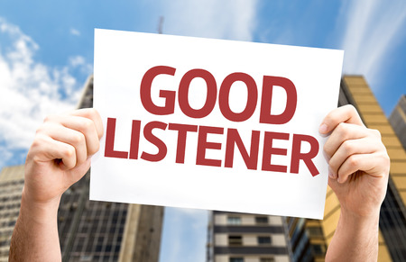 listener: Hands holding card with text Good listener on city background