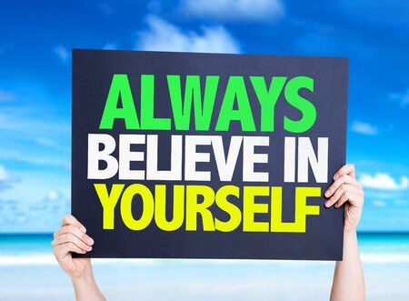 always: Hands holding cardboard with text Always Believe In Yourself on beach background Stock Photo