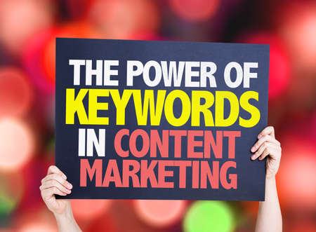 keywords background: Hands holding cardboard with text The Power of Keywords in Content Marketing on bokeh background Stock Photo