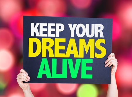 alive: Hand holding cardboard with text Keep Your Dreams Alive on bokeh background
