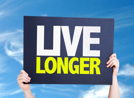 longer: Hands holding cardboard with text Live Longer on sky background Stock Photo