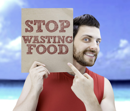 man holding card: Man holding card with text Stop Wasting Food on beach background Stock Photo