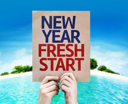 fresh start: Hands holding cardboard with text New Year Fresh Start on beach background