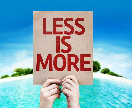 less: Hands holding cardboard with Less is More on island background Stock Photo