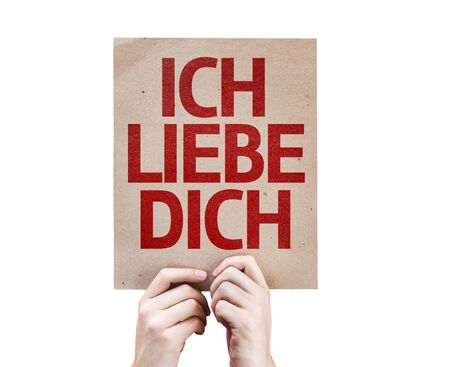 express feelings: Hands holding cardboard with I Love You in German on white background