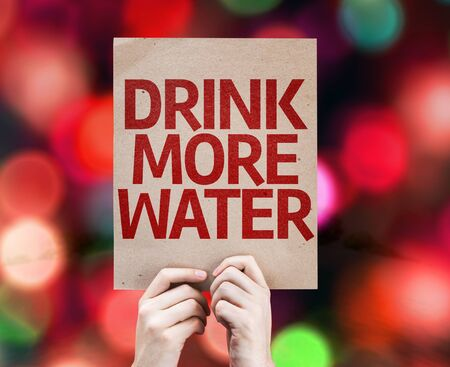 beverage display: Hands holding cardboard with Drink More Water on bokeh background Stock Photo