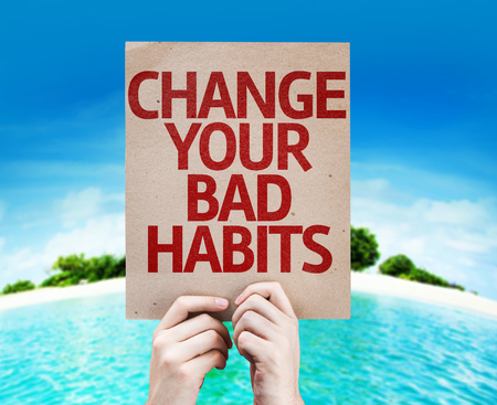bad habits: Hands holding cardboard with Change Your Bad Habits on island background Stock Photo