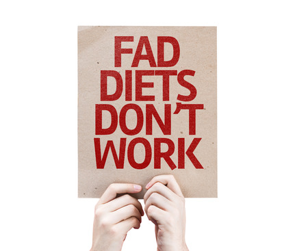 fad: Hands holding cardboard with Fad Diets Dont Work on white background Stock Photo