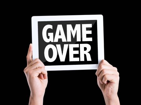 the game is over: Hands holding tablet pc with Game Over on black background