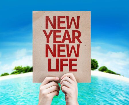 Hands holding cardboard with New Year New Life on island background