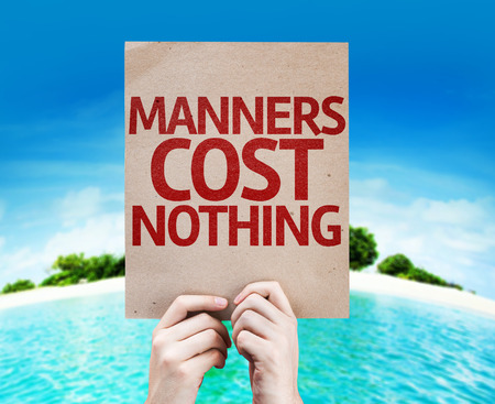 manners: Hands holding cardboard with Manners Cost Nothing on island background