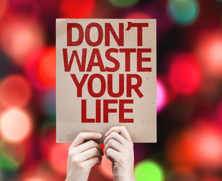 purposeful: Hands holding cardboard with Dont Waste Your Life on bokeh background Stock Photo