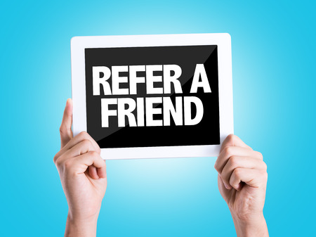 Hands holding tablet pc with Refer A Friend on blue background