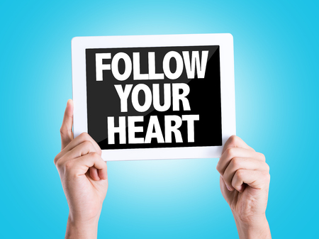 personal decisions: Hands holding tablet pc with Follow Your Heart on blue background