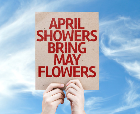 april showers: Hands holding cardboard with April Showers Bring May Flowers on sky background