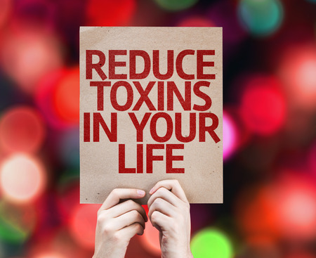 toxins: Hands holding cardboard with Reduce Toxins In Your Life on bokeh background