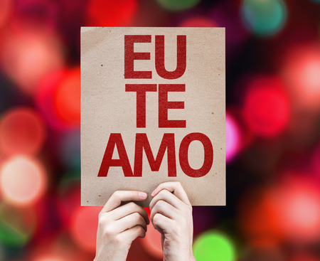 express positivity: Hands holding cardboard with I Love You in Portuguese on bokeh background Stock Photo